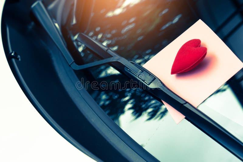 Coeur de lettre d'amour sur une note collante sous un pare-brise cru photo stock