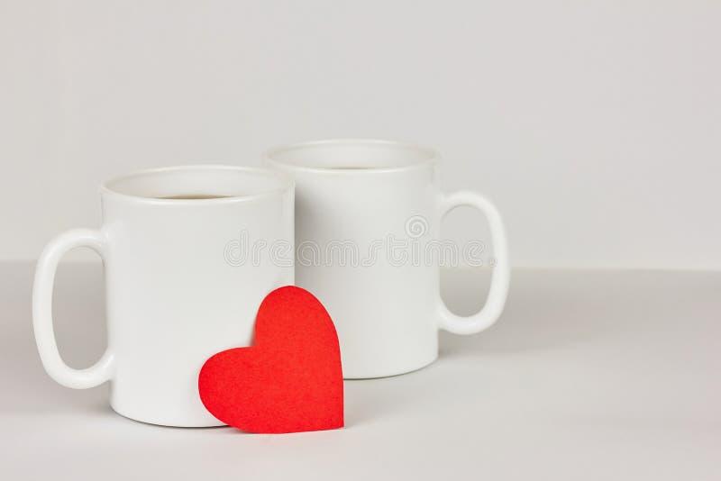 Coeur de papier rouge et deux tasses sur le fond blanc Saint-Valentin, amour, couple, épousant le concept image libre de droits
