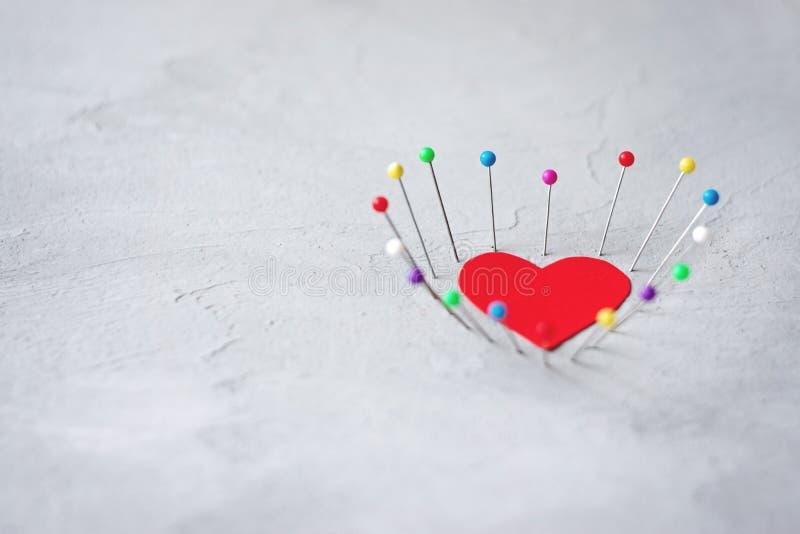 Coeur de papier rouge et goupilles de couture sur le fond gris de ciment Amour dur, solitude, divorce, concept de dissolution photo libre de droits