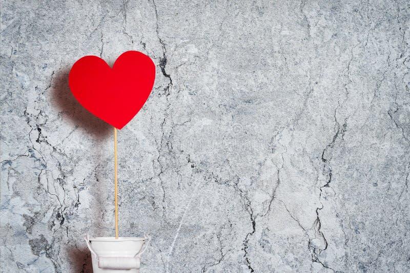 Coeur de papier rouge sur un bâton dans un seau blanc contre un mur gris Copiez l'espace Fond heureux de valentine images libres de droits