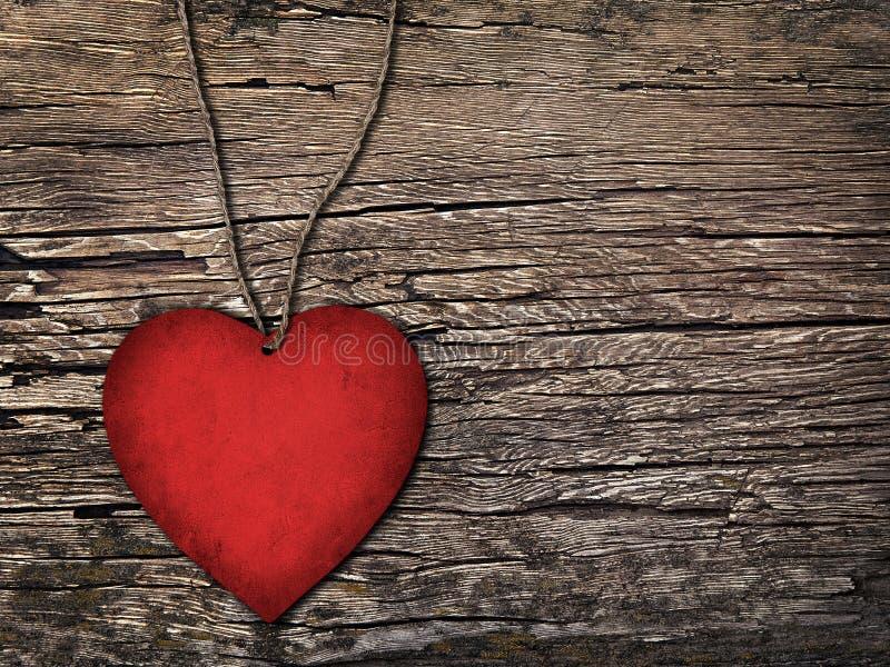 Coeur de papier rouge sur une ficelle sur le fond en bois photos stock