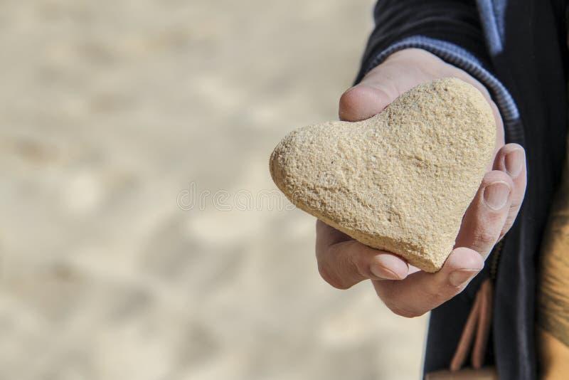 Coeur de sable dans la main photographie stock libre de droits