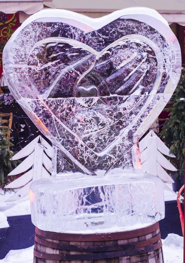 Coeur de sculpture en glace dans les mains photo stock