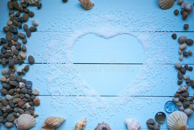 Coeur de sel de mer sur le bureau bleu-clair photos stock