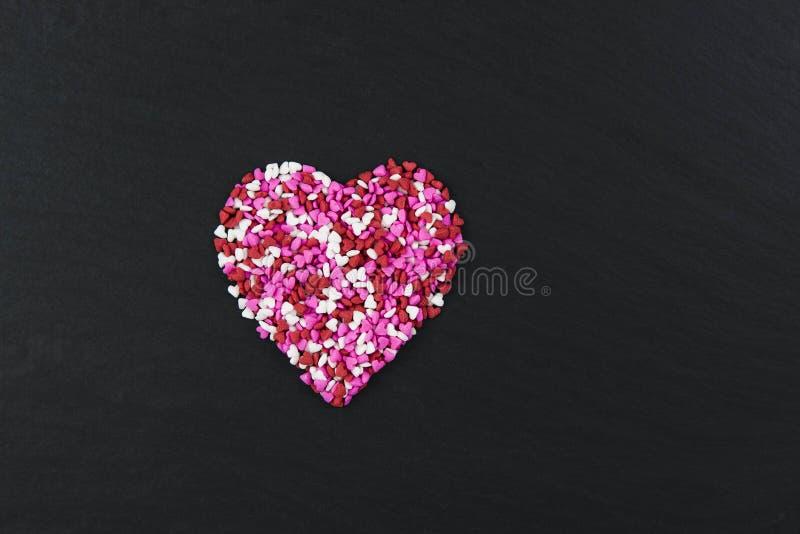 Coeur de sucrerie sur le fond noir avec de mini coeurs de sucrerie photo stock