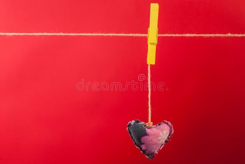 Coeur de tissu accrochant sur la corde à linge et le fond rouge avec l'espace libre photographie stock libre de droits