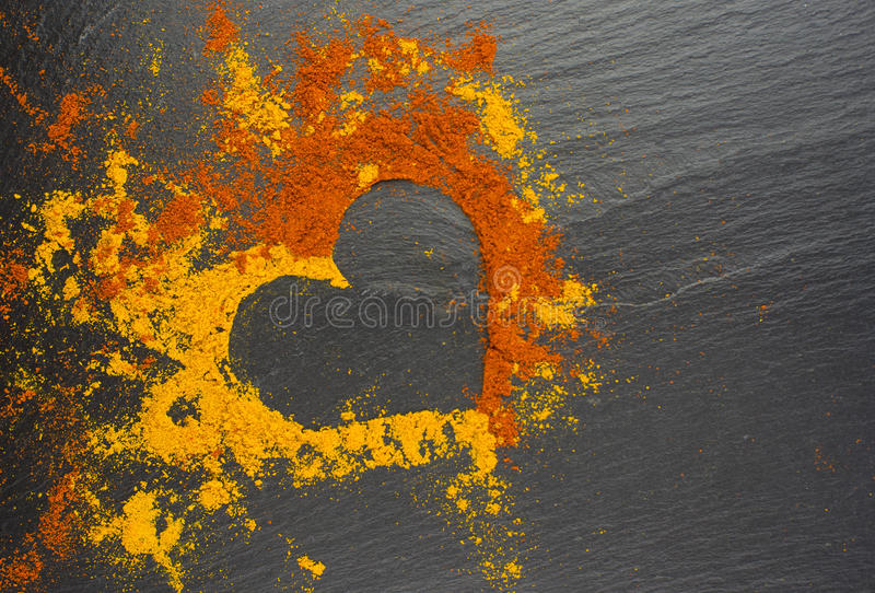 Coeur de Valentine des épices cari et paprika sur le fond noir 14 février photo stock