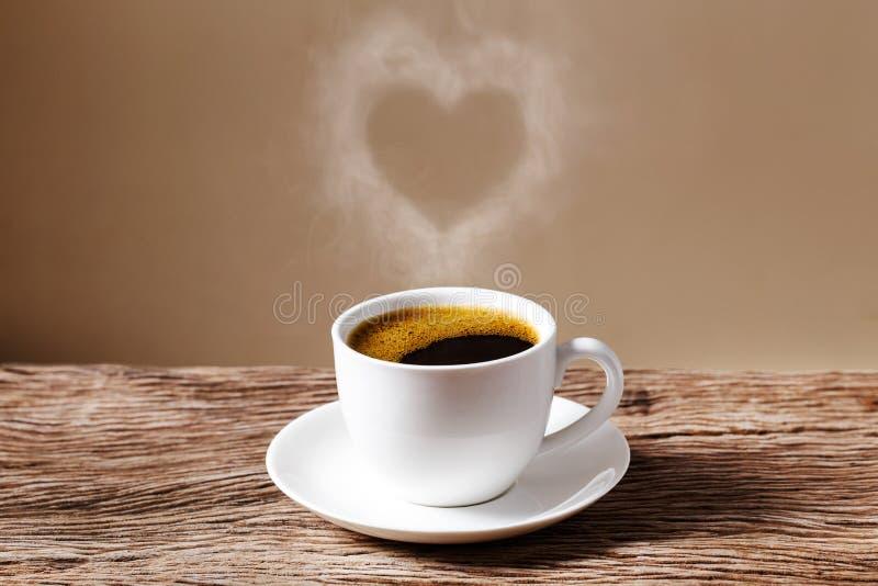 Coeur de vapeur planant au-dessus d'une tasse de café rouge de café sur la table en bois avec le fond crème de mur photos stock