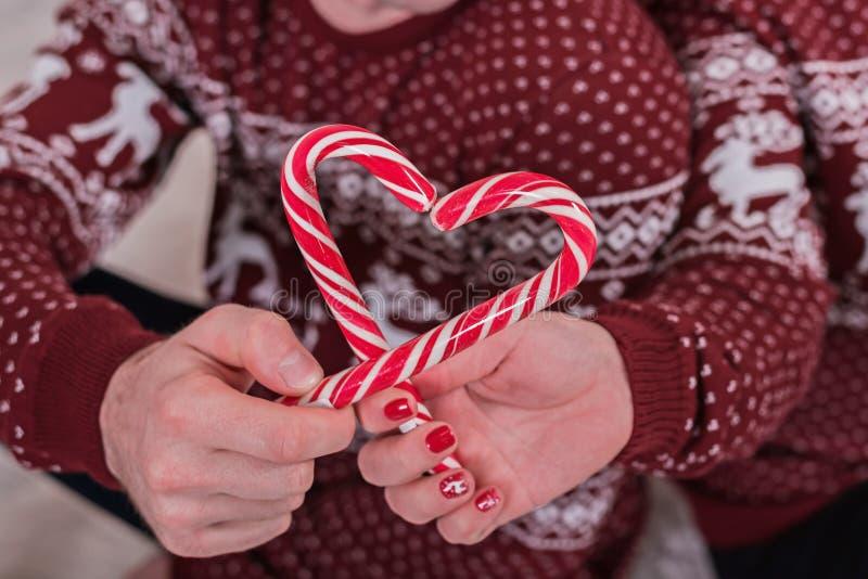 Coeur des cannes de sucrerie dans des mains des couples romantiques dans des chandails de Noël images stock