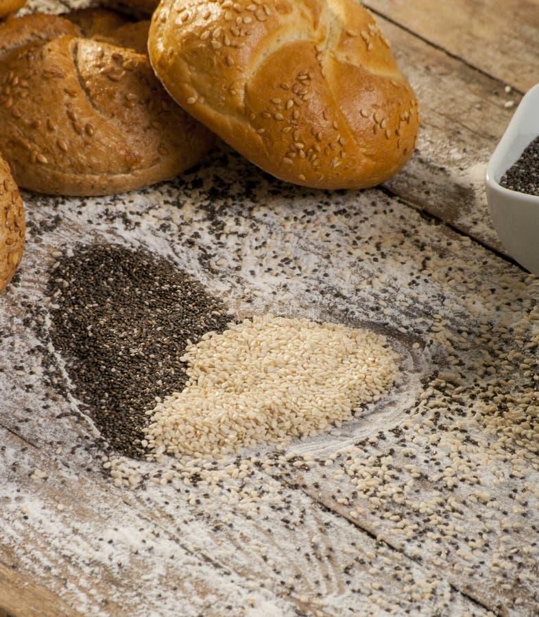Coeur des graines de sésame avec des petits pains de pain photographie stock libre de droits