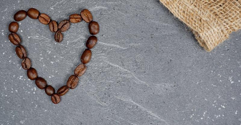 Coeur des grains de café avec la toile de jute au fond gris de plan de travail de cuisine photos libres de droits