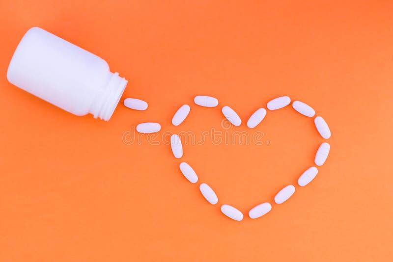 Coeur des pilules sur un fond orange Des Tablettes sont répandues sous forme de coeur d'une boîte blanche de médecine Configurati photo stock