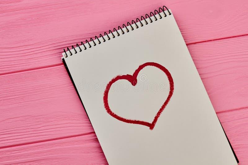 Coeur dessiné avec le rouge à lèvres rouge sur le bloc-notes de papier photos libres de droits
