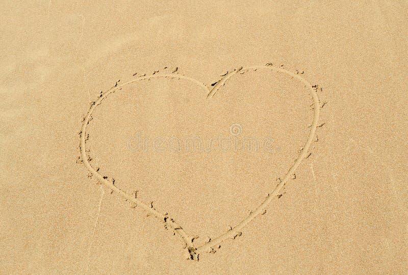 Coeur dessiné dans le sable photographie stock libre de droits