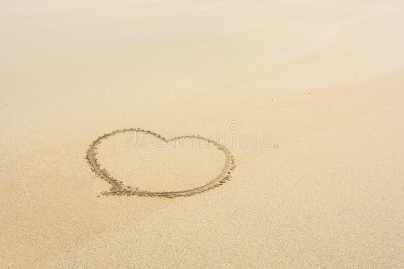 Coeur dessiné dans le sable d'une plage isolée image stock