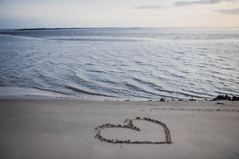 Coeur dessiné dans le sable sur la plage par la mer photos stock