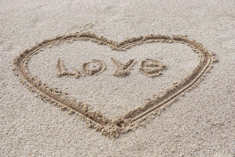 coeur dessiné sur le sable sur le bâton de plage dans l'inscrip central image stock