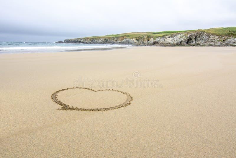 Coeur dessiné sur le sable d'une plage isolée photos stock