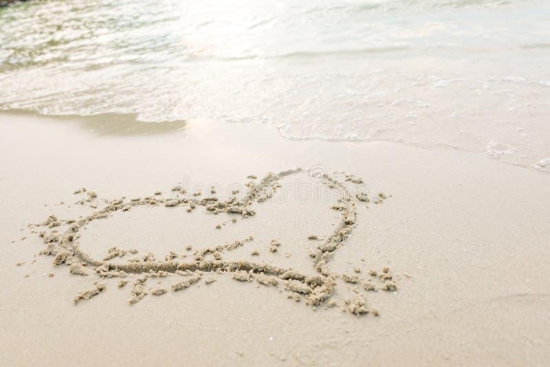 Coeur dessiné sur un sable de plage avec la vague de la mer à la lumière du soleil lumineuse image libre de droits