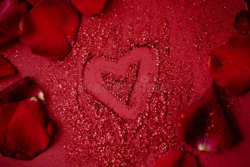 Coeur drowing rouge sur le fond rouge avec des pétales de roses rouges image stock