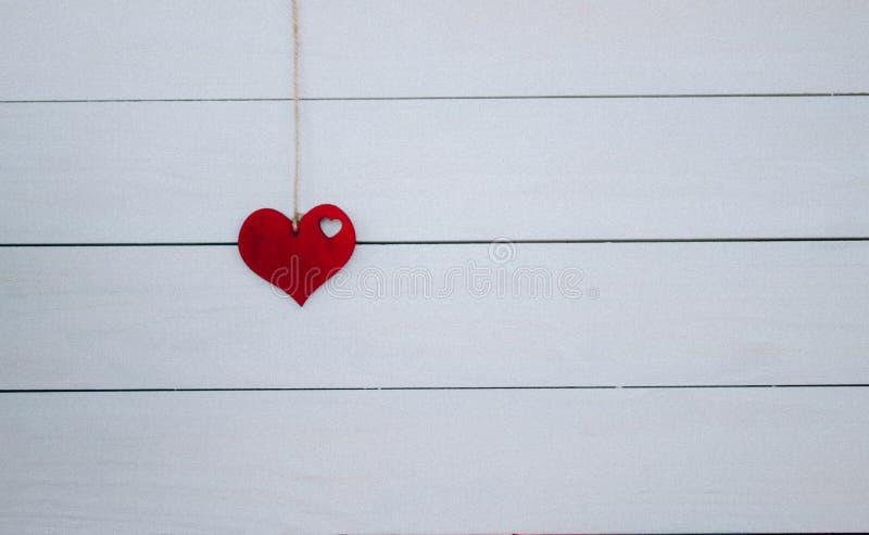 Coeur du ` s de Valentine accrochant sur la corde naturelle Fond blanc en bois Rétro type photos stock
