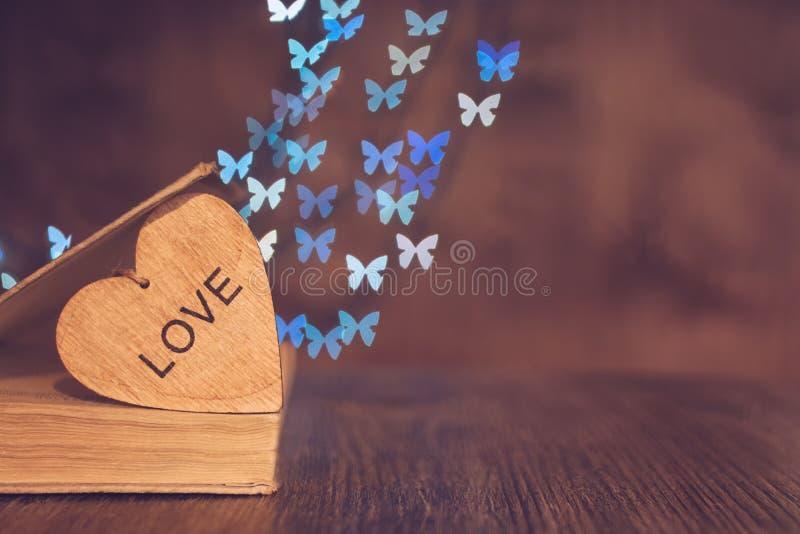 Coeur en bois avec un vieux livre sur la table et un fond de bokeh fait de papillons Jour du `s de Valentine image stock
