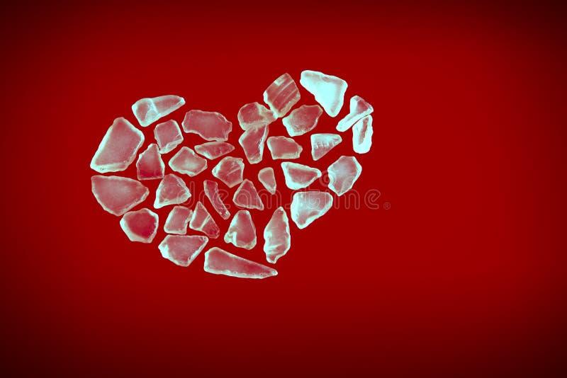 Coeur en cristal cassé sur le rouge image stock