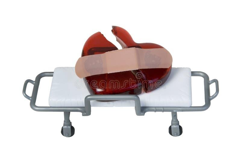 Coeur en verre rouge cassé avec le bandage sur le chariot d'hôpital image stock