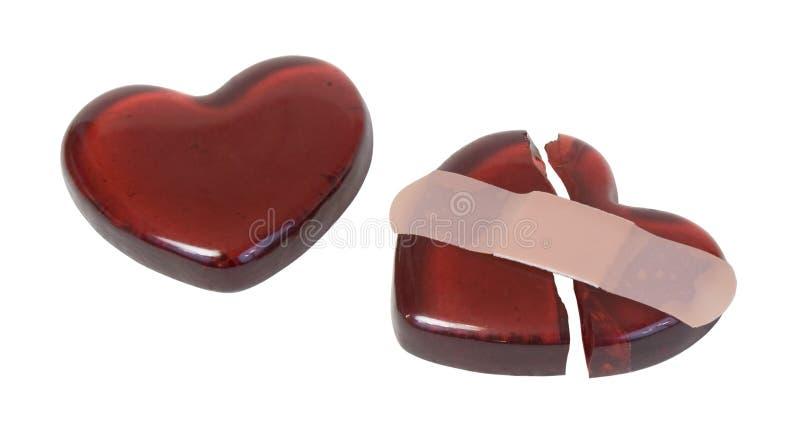 Coeur en verre rouge cassé réparé avec un bandage photo libre de droits