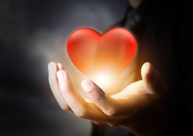 Coeur en verre rouge dans la main d'homme d'affaires images stock