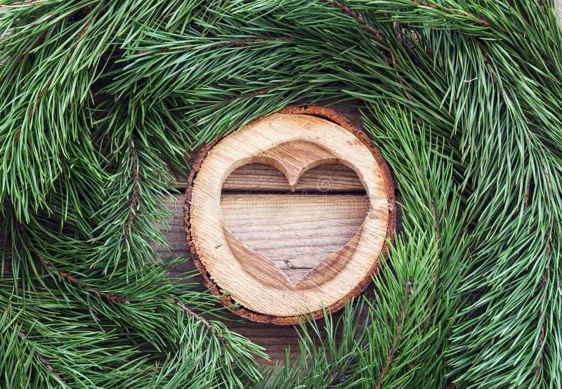 Coeur et branches de pin en bois découpés sur le vieux conseil en bois image stock