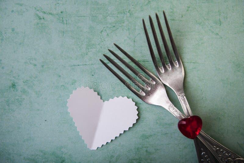 Coeur et couverts rouges sur un fond de turquoise, jour du ` s de Valentine photographie stock