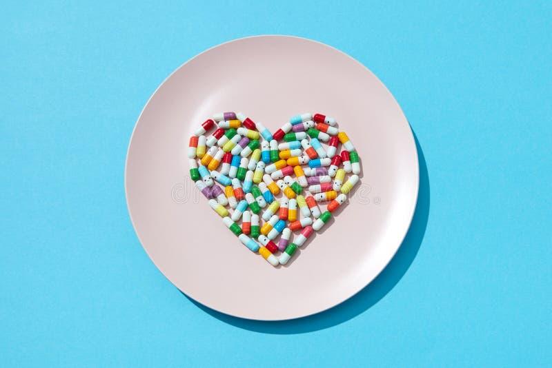 Coeur fait à partir des pilules et des capsules de médecine sur un plat blanc sur un fond bleu, l'espace de copie Complément alim photographie stock libre de droits
