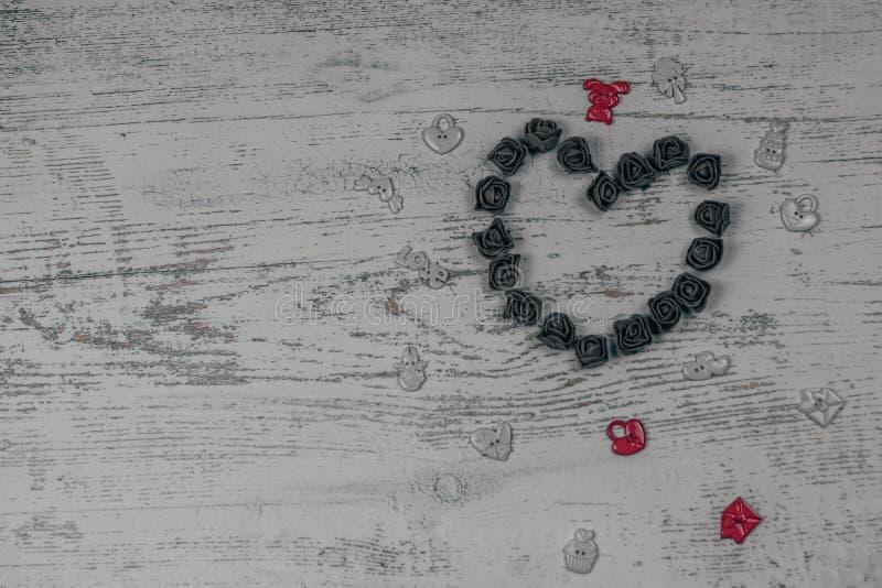 Coeur fait de roses foncées avec des jouets Sur le fond en bois, bokeh de photo Festin de l'amour, Saint-Valentin photo libre de droits