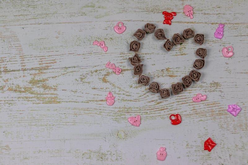 Coeur fait de roses foncées avec des jouets Sur le fond en bois, photo ci-dessus Festin de l'amour, Saint-Valentin photographie stock