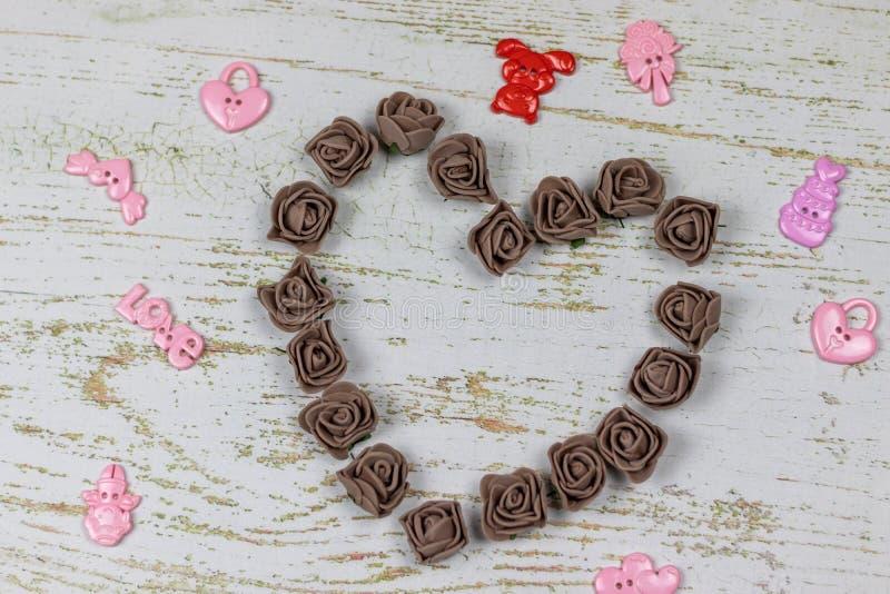 Coeur fait de roses foncées avec des jouets Sur le fond en bois, photo ci-dessus Festin de l'amour, Saint-Valentin photos stock