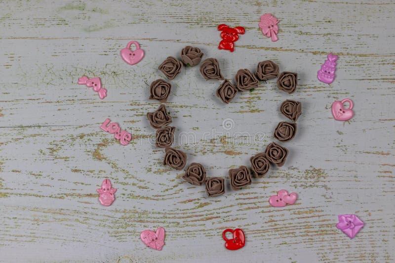 Coeur fait de roses foncées avec des jouets Sur le fond en bois, photo ci-dessus Festin de l'amour, Saint-Valentin images stock