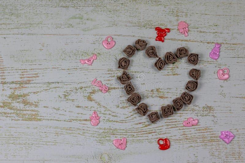Coeur fait de roses foncées avec des jouets Sur le fond en bois, photo ci-dessus Régal de l'amour Carte postale avec l'espace de  photo libre de droits