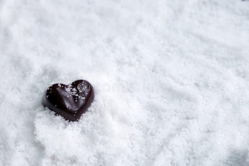 Coeur foncé de chocolat sur la neige avec l'espace de copie, concept noir de Saint-Valentin photo stock