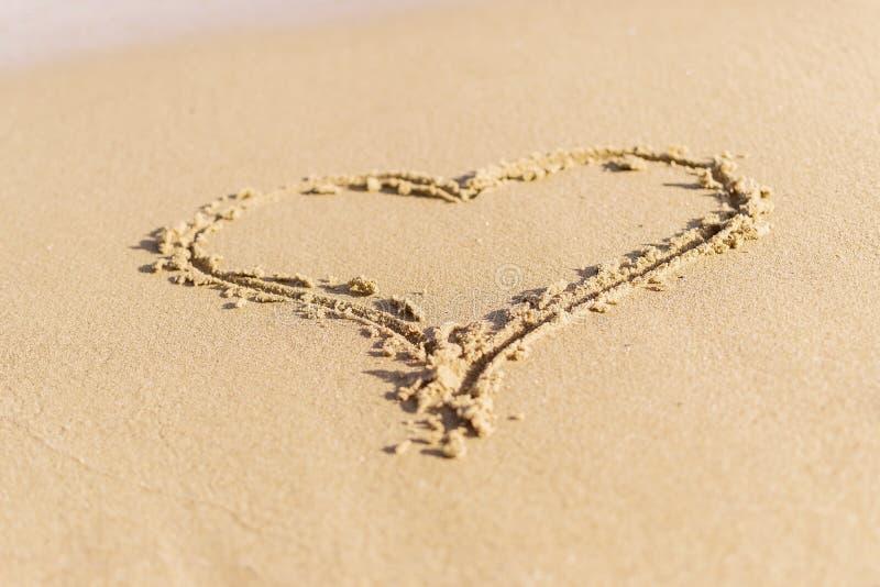 Coeur le symbole de l'amour dessiné dans le sable de mer humide Le concept de l'amour, lune de miel, vacances d'été images stock