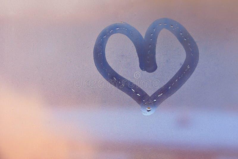 Coeur peint avec le doigt sur la fenêtre brumeuse image stock