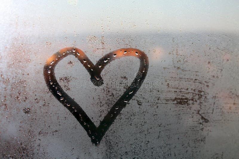 Coeur peint sur le verre de fenêtre humide photos stock