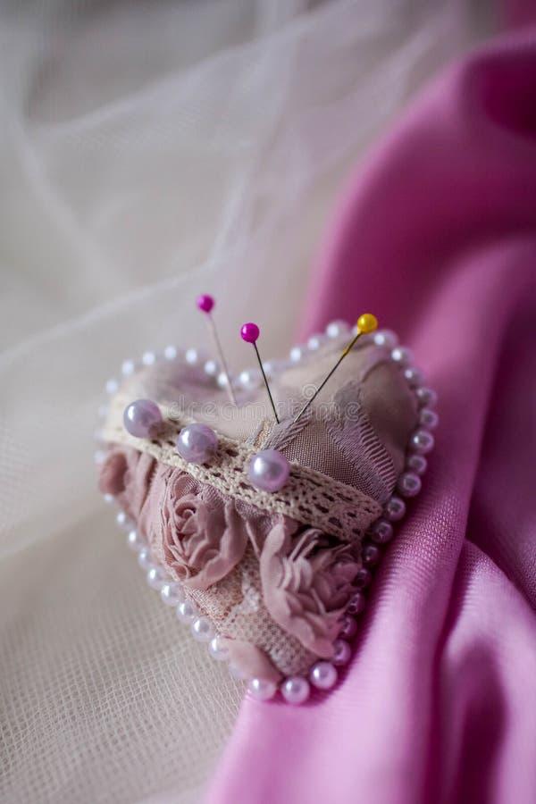 Coeur rose de pelote à épingles sur un fond clair image libre de droits