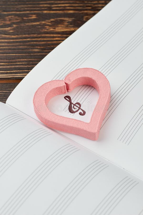 Coeur rose sur le carnet musical photos stock
