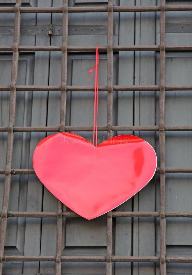 Coeur rouge accrochant sur la grille la Saint-Valentin photographie stock