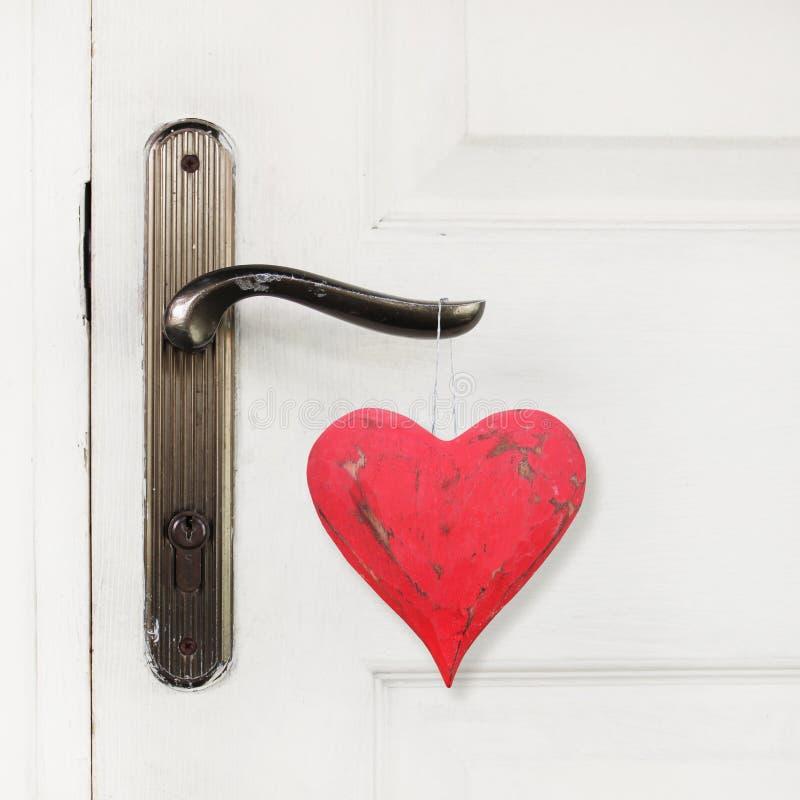 Coeur rouge accrochant sur la poignée de porte image stock