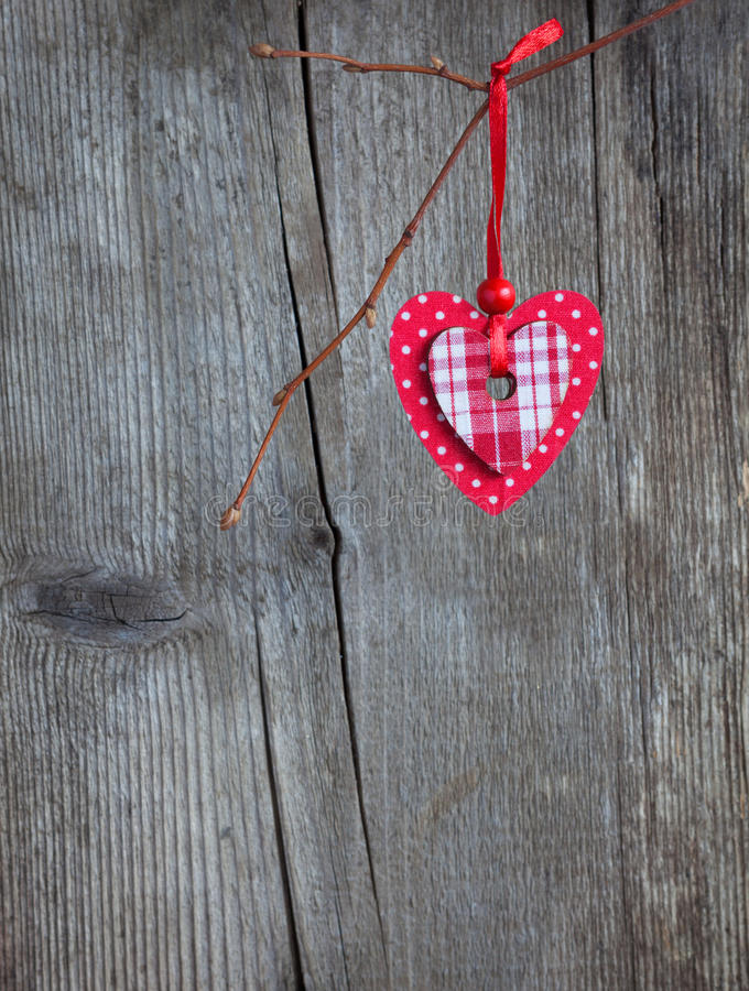 Coeur rouge, accrochant sur une branche au-dessus du fond en bois grunge photos libres de droits