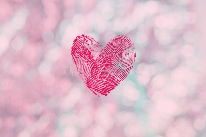 Coeur rouge d'empreinte digitale pour le jour de valentines sur le fond rose-clair de bokeh, papier peint pour le jour des femmes images libres de droits