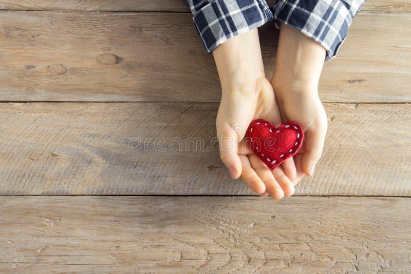 Coeur rouge dans des mains photographie stock