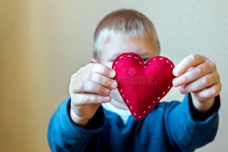 Coeur rouge dans des mains d'enfant photos stock